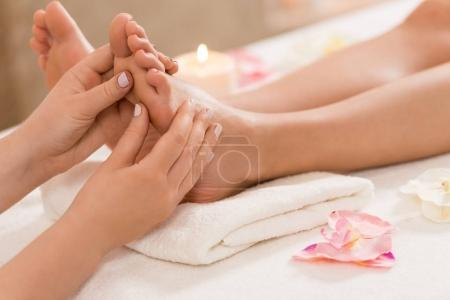 Massage therapist making feet massage