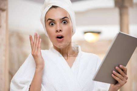 Shocked woman using digital tablet