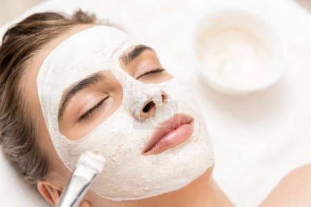 Cosmetologist applying facial mask