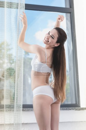 Woman opening curtains in morning