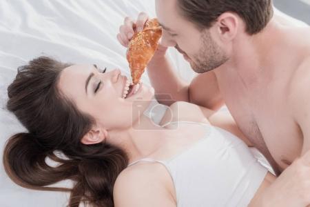 Man feeding his girlfriend in bed