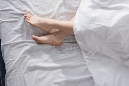 Female feet stretching out of blanket