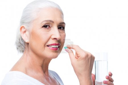 Senior woman with pill