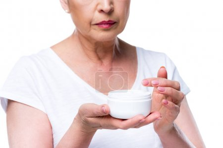 Senior woman with face cream