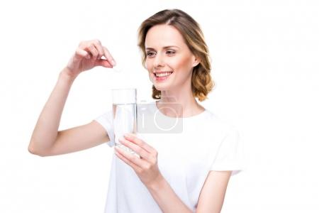Woman with glass of water and pill