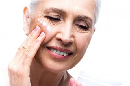 Senior woman applying cream