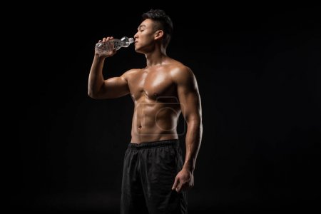 Shirtless sportsman drinking water