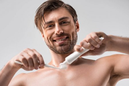 Smiling man with toothbrush and toothpaste