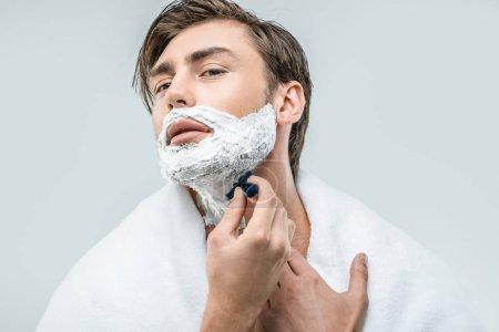 Man in foam shaving with razor