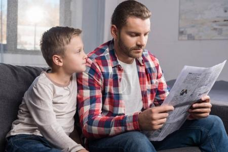 father and son reading at home