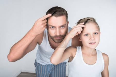 father and son combing hair