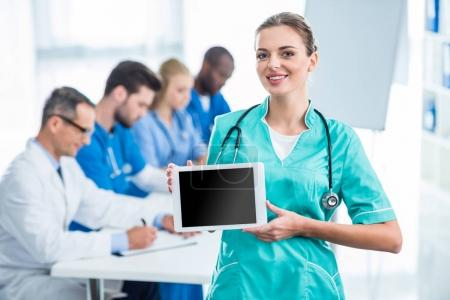 Young nurse holding tablet
