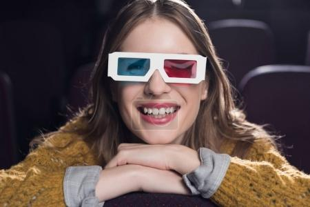 young smiling woman in 3d glasses watching movie in cinema