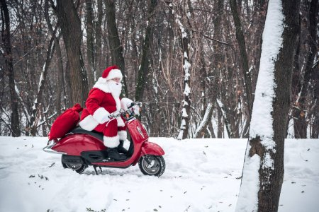 Photo for Side view of Santa Claus riding on red scooter with bag full of gifts in winter forest - Royalty Free Image
