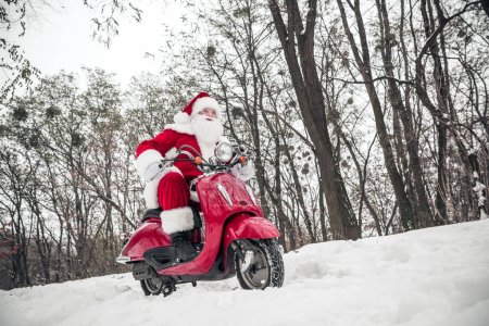 Photo for Low angle view of Santa Claus riding on red scooter in winter park - Royalty Free Image