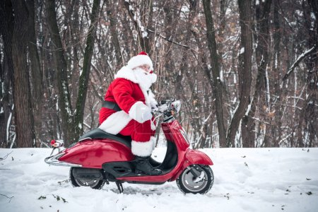 Photo for Side view of Santa Claus riding on red scooter in winter park - Royalty Free Image