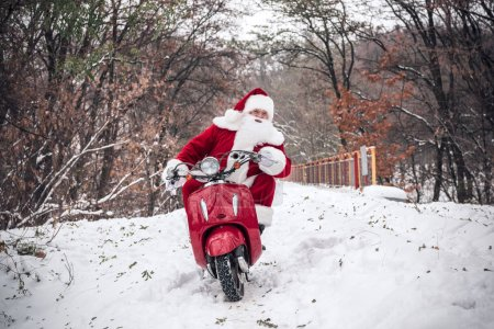 Photo for Front view of Santa Claus riding on red scooter in winter park - Royalty Free Image