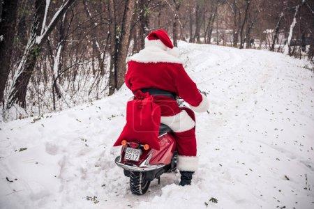 Photo pour Vue arrière du Père Noël chevauchant sur scooter rouge avec Nouvel An 2017 signe et sac plein de cadeaux - image libre de droit
