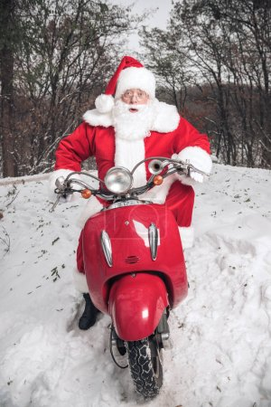 Photo for Portrait of Santa Claus riding on red scooter and looking at camera in winter park - Royalty Free Image