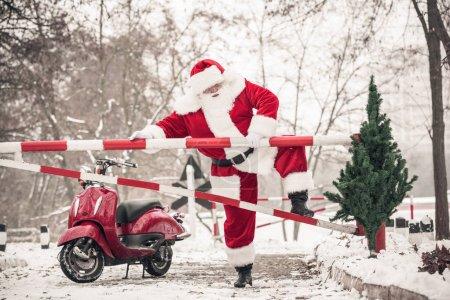 Santa Claus climbing over barrier