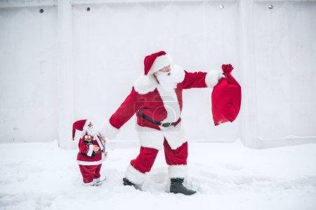 Santa Claus walking with little Santa