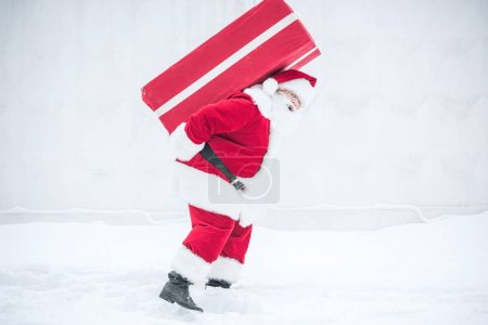 Photo for Side view of Santa Claus carrying big gift box on his back - Royalty Free Image