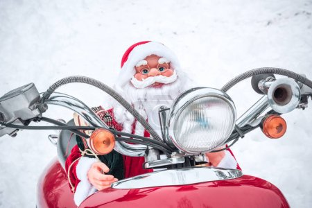 Photo for Closeup view of Santa Claus toy riding on red scooter - Royalty Free Image