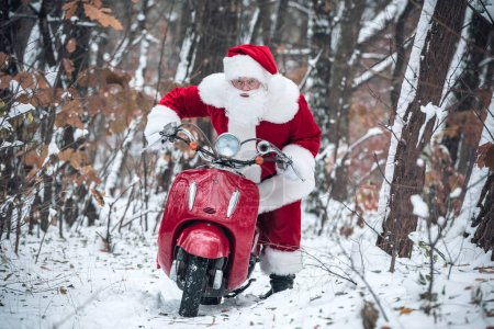 Photo for Santa Claus riding red scooter and looking at camera on snowy trail - Royalty Free Image