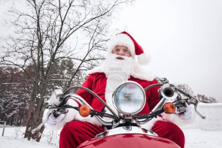 Santa Claus riding red scooter