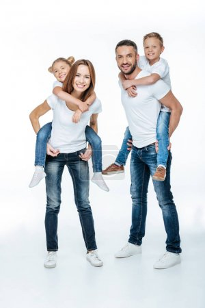 Photo for Smiling parents piggybacking happy children isolated on white - Royalty Free Image