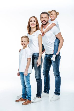 Photo for Happy family in white t-shirts and jeans standing together and looking at camera isolated on white - Royalty Free Image