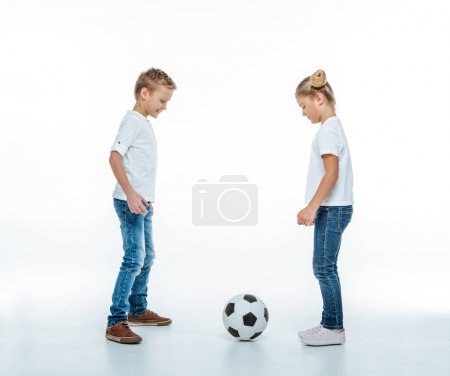 Photo for Full length portrait of two smiling children in white t-shirts and jeans playing with soccer ball isolated on white - Royalty Free Image