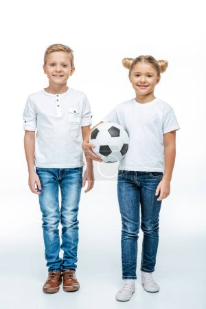 Smiling children standing with soccer ball