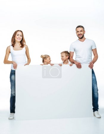 Photo for Happy family in white t-shirts holding blank card isolated on white - Royalty Free Image
