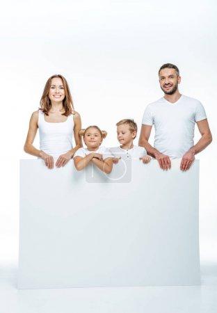Photo pour Famille joyeuse en t-shirts blancs tenant carte blanche vierge et regardant la caméra isolée sur blanc - image libre de droit