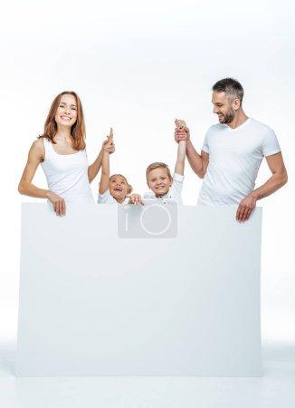 Photo pour Famille souriante en t-shirts blancs tenant carte blanche vierge et s'amusant isolé sur blanc - image libre de droit