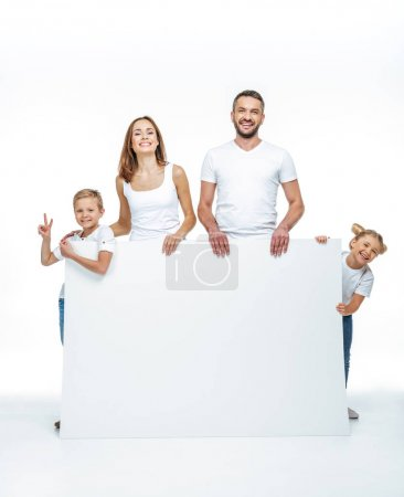 Photo for Happy family in white t-shirts holding blank card and looking at camera isolated on white - Royalty Free Image