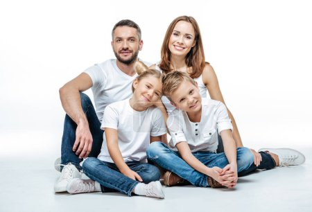 Photo for Happy family with two children sitting together and looking at camera isolated on white - Royalty Free Image