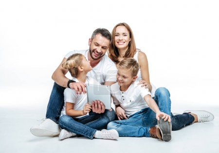 Photo for Smiling family in white t-shirts and jeans sitting together and using digital tablet isolated on white - Royalty Free Image