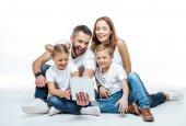 """Постер, картина, фотообои """"Улыбающаяся семья с помощью цифрового планшета"""""""