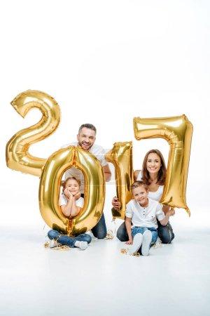 Photo pour Heureuse famille tenant doré 2017 ballons signe et regardant la caméra isolée sur blanc - image libre de droit