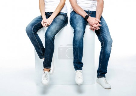 Photo for Low section of young couple sitting in jeans and white shoes isolated on white - Royalty Free Image