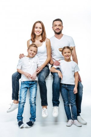 Photo for Happy parents with two children in white t-shirts and jeans having fun together and looking at camera isolated on white - Royalty Free Image