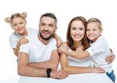 A fehér pólók ölelgetés családi mosolyogva