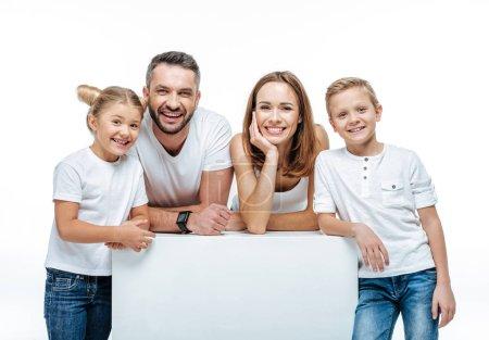 Photo pour Famille joyeuse avec deux enfants debout ensemble et regardant la caméra isolée sur blanc - image libre de droit