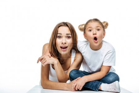 Photo for Shocked mother and daughter looking at camera isolated on white - Royalty Free Image