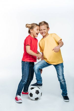 Photo pour Full length view of Happy siblings in colored t-shirts standing with soccer ball isolated on white - image libre de droit