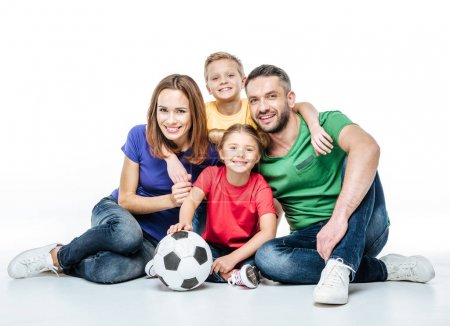 Photo for Happy family in colored t-shirts sitting together with soccer ball isolated on white - Royalty Free Image