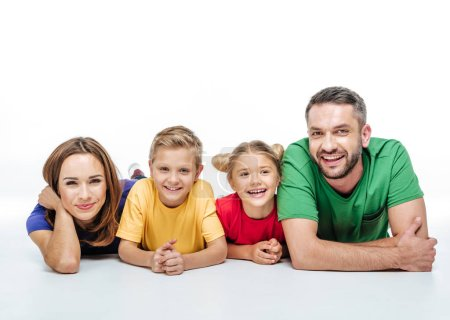 Foto de Happy family in colored t-shirts lying together and having fun isolated on white - Imagen libre de derechos