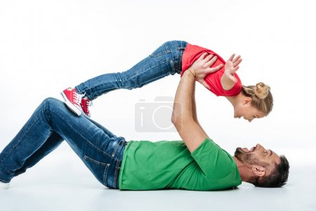 Photo pour Happy father and daughter having fun together while lying on floor isolated on white - image libre de droit